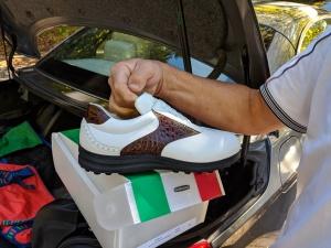 Übergabe auf dem Golfplatz-Parkplatz: weiß-brauner Herrenschuh